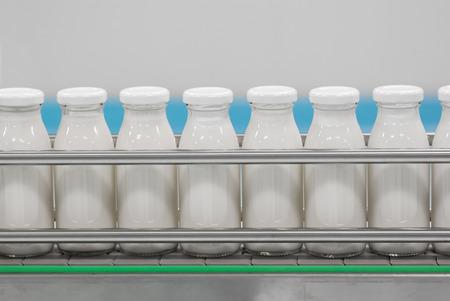 lineas verticales: Transportador con las botellas de vidrio llenas de los productos lácteos