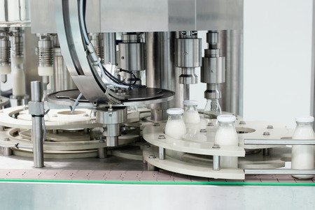 milk production: Conveyor with glass bottles filled with milk products Stock Photo