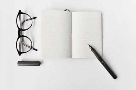 Journal vierge, stylo et lunettes sur fond blanc Banque d'images