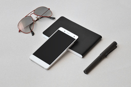 Smart phone, notebook, sunglasses, and pen, isolated