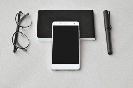 Smart phone, notebook,  eyeglasses, and pen, isolated Stock Photo