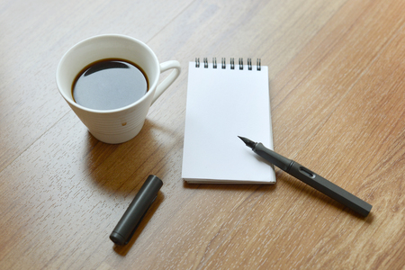Coffee cup, spiral notebook and pen on the laminate floor background - taken in natural light  to create realistic indoor mood Stock Photo