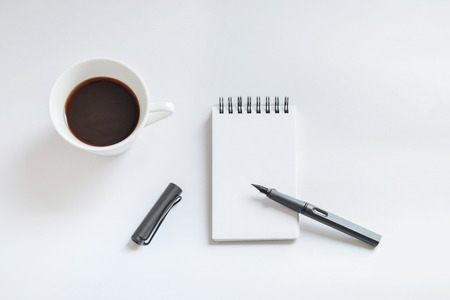 Coffee cup, spiral notebook and pen on white background - taken in natural light with strong shadow to create realistic indoor mood