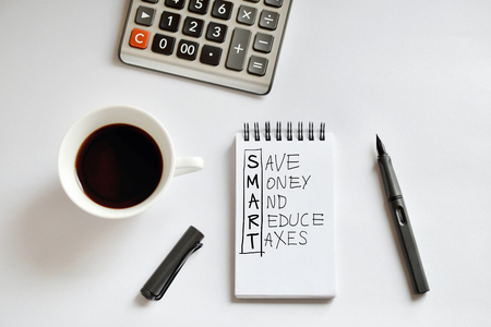 Coffee cup, spiral notebook, calculator, and pen on white background, with handwritten Save Money And Reduce Taxes- taken in natural light with strong shadow to create realistic indoor mood Stock Photo