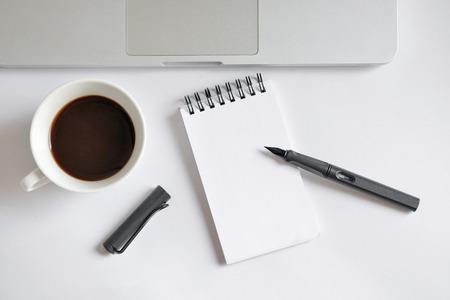 filiżanka kawy: Filiżanka kawy, spiralna notebooka, klawiatury komputera i pióra na białym tle - wykonane w naturalnym świetle z silnym cieniu stworzyć realistyczną kryty nastrój