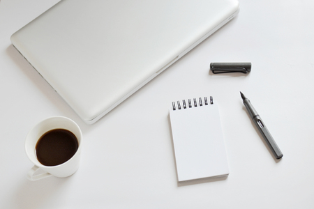 Coffee cup, spiral notebook, laptop, and pen on white background -taken in natural light with strong shadow to create realistic indoor mood