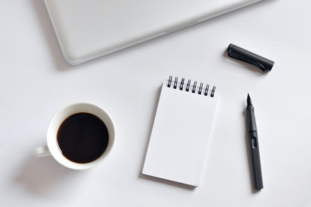Coffee cup, spiral notebook, laptop, and pen on white background - taken in natural light with strong shadow to create realistic indoor mood