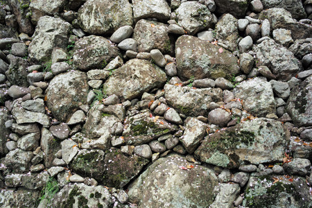Ancient wall of round and crushed stones with moss Stock Photo