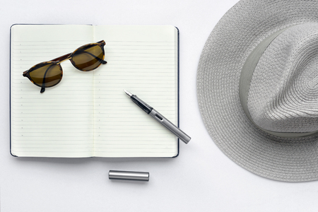 Sunglasses, notebook, pen, and hat, on white background - taken in natural light with strong shodow to create realistic indoor mood Stock Photo