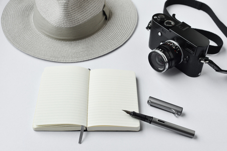 Notebook, pen, and camera, on white background - taken in natural light with strong shodow to create realistic indoor mood