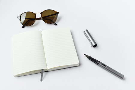 Sunglasses, notebook, and pen, on white background - taken in natural light with strong shodow to create realistic indoor mood Stock Photo