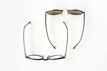 Top view of sunglasses and reading glasses on white background. Represents work and vacation Stock Photo