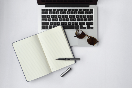 Sunglasses, notebook, pen, and computer keyboard on white background - taken in natural light with strong shodow to create realistic indoor mood