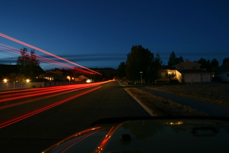 a long streak of red lights is left as the vehicle passes and leaves a trail