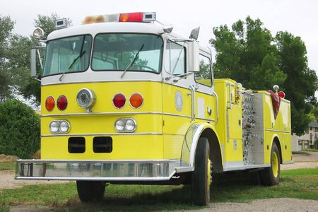 lightbar: A big bright yellow retired fire engine sits along side the firehouse Stock Photo