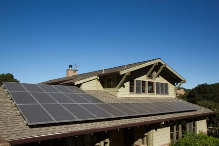 solar panels on roof of house. horizontal orientation, blue sky, gray panels on brown roof. room for copy