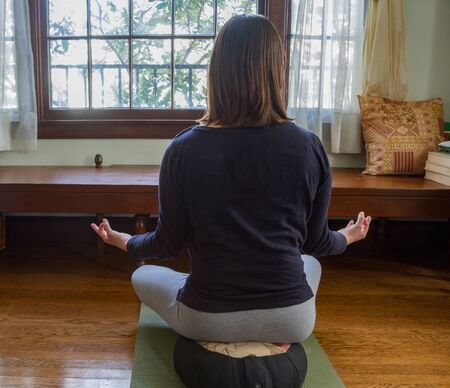 Young woman sitting in mediation pose on cushion on wood floor inside a home with window in front of woman. Trees seen outside window. Woman turned away from viewer. Room for copy.