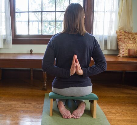 Young woman sitting in mediation or yoga pose on cushion on wood floor inside a home with window in front of woman. Trees seen outside window. Woman turned away from viewer. Room for copy.