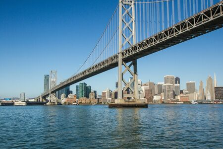 color horizontal photo of bay bridge in san francisco California, USA. photo taken from boat that is about to pass under bridge with san francisco skyline in background. water in foreground Reklamní fotografie
