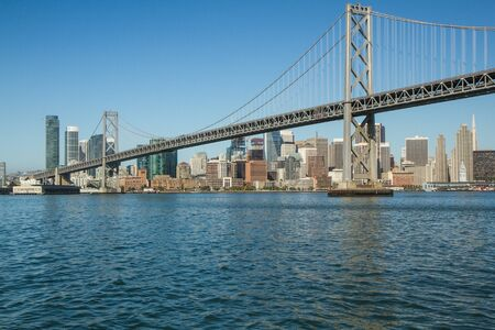 view of approach to Bay Bridge, San Francisco, California, USA, as seen from ferry boat, with city in background. daytime horizontal photo copy space