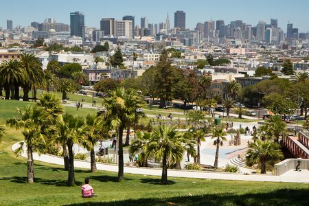 Dolores Park, San Francisco, California. color landscape photo of park with palm trees in foreground and san francisco skyline in background