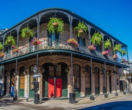 French Quarter architecture in New Orleans, Louisiana. House in French Quarter in 18th century Spanish style with cast iron galleries with hanging plants and pastel colors. Reklamní fotografie