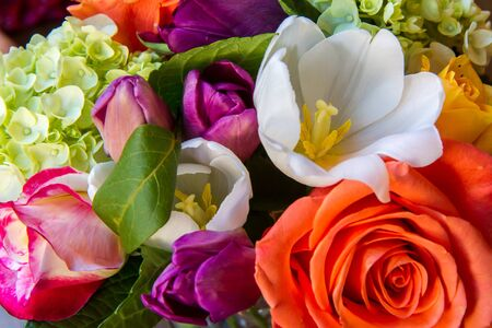 Closeup of multicolored flower arrangement from above. Orange  and pink rose, green hydrangea, white lily, purple tulips
