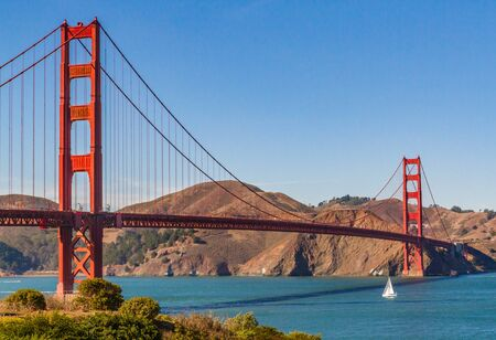 Golden Gate Bridge, San Francisco, California, USA. Single white sailboat about to pass under the bridge. Space for copy in blue sky, no clouds.