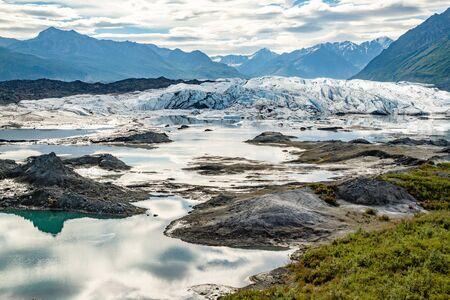 Matanuska Glacier in Alaska, USA. Color landscape photo of Matanuska glacier in the late morning sun with glacier and sky reflected in water.