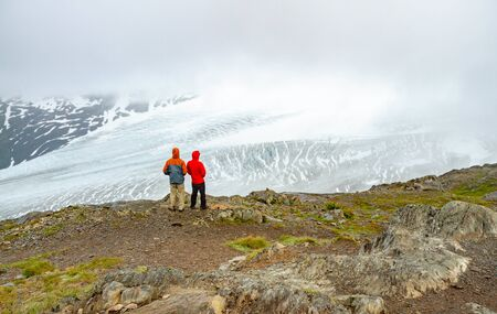 Two hikers standing on the Harding Icefield Trail in Alaska, USA, gazing at Exit Glacier. One hiker is wearing a red jacket, the other is wearing an orange jacket. Hikers have their back to the viewer Reklamní fotografie