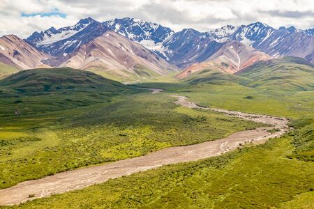 Denali National Park, Alaska, USA. Dry riverbed winding through valley with mountains in background. Reklamní fotografie