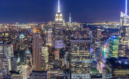 New York City skyline at night as seen from the Top of the Rock. Empire State Building in center of frame Freedom Tower in distance.