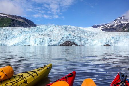 Tips of kayaks in water in front of Aialik Glacier, Aialik Bay, Alaska, USA. Tips of kayaks in foreground, glacier in background.