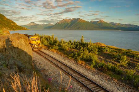 Alaska Denali Star train passing along tracks next to lake with mountains in background in Alaska, USA.Train and landscape bathed in golden light.