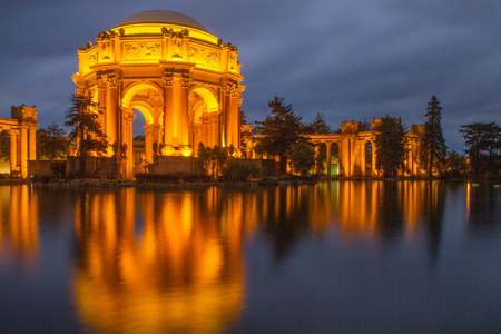 Palace of Fine Arts, San Francisco, California, USA. Night photo of Palace of Fine arts in golden light with reflection in water, gray sky.