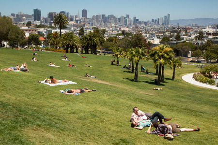 Dolores Park, San Francisco, California, USA. Palm trees in the foreground, buildings in the background, blue sky, no clouds, landscape orientation, midday.