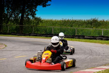 Two people competetively racing with go karts photo