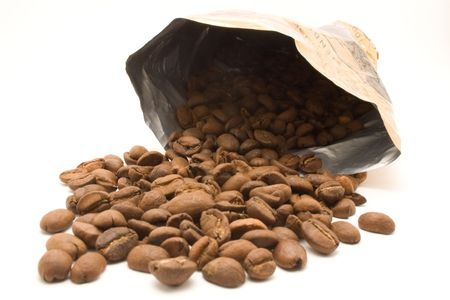 Coffee beans spilling out of a coffee bag on white photo