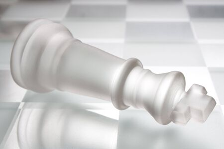 Defeated king on a chess board photo