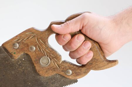 A hand holding a saw