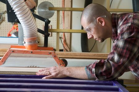 Woodworker working on table saw Stock Photo