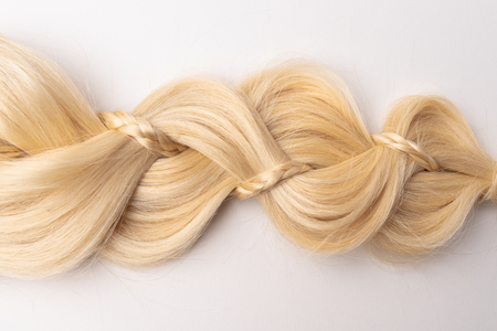 Human, natural light blond hair tress on white isolated background. An example of a fashionable hairstyle for a poster or an hairdressing website.