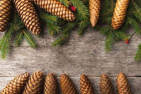 Winter holiday background with fir, pine tree and cones decoration on dark wooden board. Composition with copy space for text. Flat lay, top view