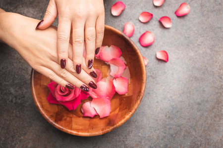 Spa Salon: Beautiful Female Hands with painted gel hybrid nails in the Bamboo, Wooden Bowl of Water with Red Roses and Rose Petals on the rustic background. To view.