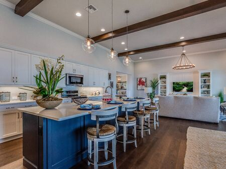 Long white kitchen with a blue wood kitchen island