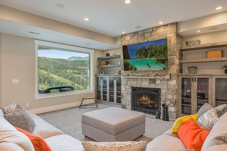 Living room with stone fireplace and awesome mountain views