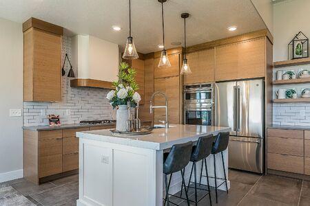 Sleek white kitchen island amongst modern light brown cabinetry Stock Photo