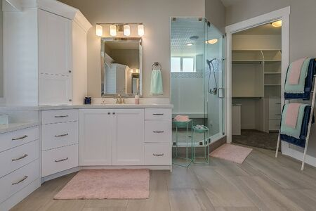 Green and pink colors accent this large white master bathroom
