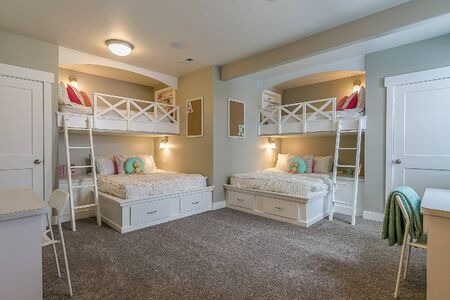 Girls bedroom with four bunk beds and little desk Archivio Fotografico