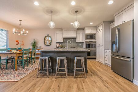 Mostly white kitchen with island and dining area nearby